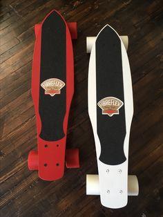 (Red skateboard) G&S Fibreflex Henry Hester slalom deck, gold Gull Wing HPG Trucks (70s), rare first-generation red Kryptonics wheels (70s); (White skateboard): G&S Fibreflex Henry Hester slalom deck; chrome-polished Gull Wing HPG trucks (70s); Road Rider 6 wheels (modern).