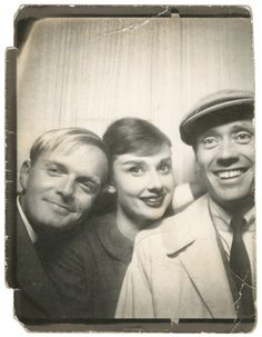 an old  black and white photobooth photo of truman capote, audrey hepburn, and her then husband mel ferrer. this was probably taken in the late 50s, early 60s, around the filming of breakfast at tiffany's