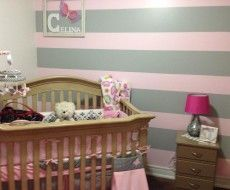 Baby Nursery Ideas:  An adorable pink nursery that oozes of designer style. The grey and pink coloured stripes on the wall  complements the contemporary customised name artwork, to give the nursery a personal touch.   What a perfect calm haven for a baby girl. #babyroom #girl