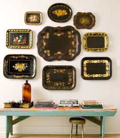 An assortment of black Toleware trays create a stunning art installation in the sitting room of this Connecticut cottage. Encircling the largest one with trays of varying scale creates a cohesive look among the mismatched patterns.