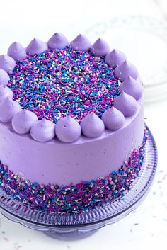 Moist layers of flavourful black velvet cake filled with fluffy cream cheese filling and fresh blackberries, frosted in gloriously purple vanilla bean frosting and finished with Sweetapolita Galaxy Twinkle Sprinkle Medley and buttercream poofs.