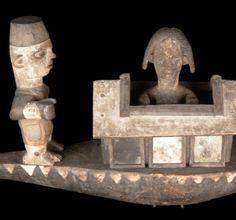 """Kana Bois polychrome. 77 x 39,5 x 19 cm. Cette pièce est un exemple raffiné du style de l'école de Barako, probablement de la main de Sagbara. Deux personnages masculins, l'un en uniforme, l'autre nu, assis et tenant une pagaie, se dressent à chaque extrémité de la barque. Au centre, une tête de femme emerge de la figuration en réduction d'une maison. Il s'agit de l'image d'une jeune fille dans la maison de réclusion où elle est mise à """"engraisser"""" à l'occasion des rites marquant le passage…"""
