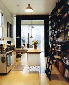 kitchen + floor to ceiling shelves with sliding ladder + black crown moulding framing the window.