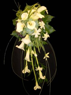 This wedding bouquet is calla lillies with singapore orchid accents, succulents, viburnum berries and bear grass trails for movement.