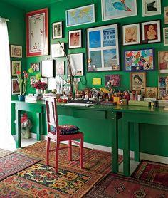 O escritório do diretor de arte e de cinema Thiago Bastos tem paredes verde-esmeralda com muitos quadros. No chão, uma composição de tapetes pequenos aquece o ambiente