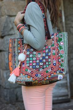 light coloured outfit with pops of colour in the bag and layered bracelets