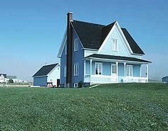 old blue farmhouse with sharp peaked roof and dormer