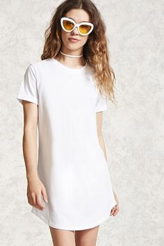 A knit dress featuring a mini cut silhouette, crew neck, cuffed short sleeves, and curved hem.