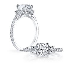 LAUREN II is a handcrafted engagement ring, set in Platinum with a Cushion cut diamond, 2 brilliant cut trapezoids and 1 row of diamonds on the band. #cushoincutdiamond #cushioncut #diamond #engagementring #cushiondiamond #threestonesetting