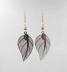 Boucles d'oreilles fantaisie en métal argenté agrémentées d'une perle de verre nacrée bronze, et de fines feuilles argentées. S'attachent grâce à des crochets d'oreille en m…