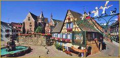 Photo panoramique au mois d'aout de l'enseigne d'Alsace qui domine la place du Château Saint-Léon, dans le centre historique d'Eguisheim. Photos des plus beaux villages de France, photos d'Eguisheim, visiter Eguisheim le village préféré des français.