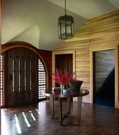 The entry's warm wood is in keeping with the home's sylvan setting | archdigest.com