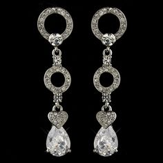 "Beautiful and alluring, these silver dangle earrings are captivating. With its lovely antique silver plating that creates two circles, a small heart shaped design encrusted by clear rhinestones and a beautiful pear cut cubic zirconia crystal, you can't go wrong. Perfect for weddings, proms or any upcoming elegant affair where you would like to show off some glam.Size: 2.5"" (Length) .5"" (Width)"