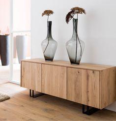 Opbergruimte niet mooi? Combineer houten dressoirs met gekleurde mooie glazen vazen en een herfsttak