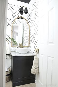 black and white stenciled powder room with black cabinet, white vessel sink, marble counter and gold accents