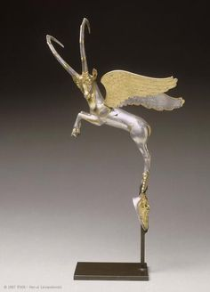 Vessel handle in the form of a winged ibex with its hooves resting on a mask of Silenus. Date: 4th century BC Location: Louvre Museum