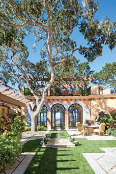 This Spanish Colonial–style home in Pebble Beach, California, received a sumptuous makeover from design firm JP Molyneux Studio. The courtyard, shown here, is outfitted with a Michael Taylor Designs table and McKinnon and Harris chairs; the hand-painted tilework around the arches is by Atelier Prométhée. Bernard Trainor + Assoc. consulted on the landscape design.