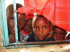 Kids in Mathare Slum, Nairobi, Kenya, looking through a window.  Read about how WALK AGAINST CRIME is helping their community...