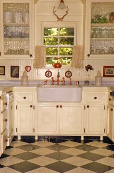 Cottage style kitchen in buttercream and red at Brambly Home and Garden. The rippled glass cabinet doors look great with the farmhouse sink.