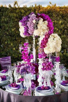 Es un hermoso arreglo como centro de mesa con orquídeas, se destacan os  colores lilas, moradas y blancas.