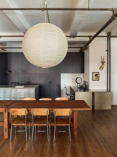 """An Isamu Noguchi pendant dominates the communal area, where a 16-foot-long farmhouse table is surrounded with vintage American school chairs. """"Like a family dining table, it's our studio's home base,"""" says Beckstedt."""