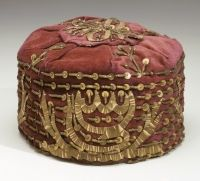 Skullcap Ottoman Empire, 19th century      Velvet: embroidered with metallic thread; sequins   More information  The small size of this skull cap indicates it was made for a child. The sprigs formed of braid terminating in blossoms (sequins) appear on Judaica textiles from Ioannina dated to the 19th century. The candelabrum motif along the side is unusual.  Source: The Non-Western Textile Cataloging Project