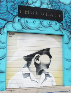 A mural by El Mac on the garage door, surrounded by new work by artist David Quan at The Chocolate Factory on Grand Avenue in downtown Phoenix.