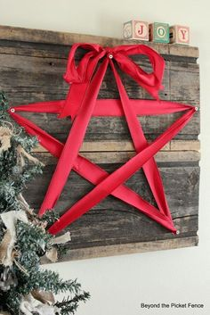 Christmas DIY - create a wall hanging with old wood (as pallets); press in stick pins to form design points, connect points with ribbon & top with bow!