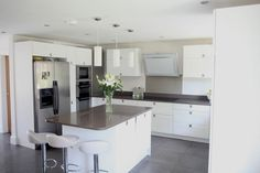 tall units and a bridging unit frames the american fridge freezer to incorporate it visually into the kitchen