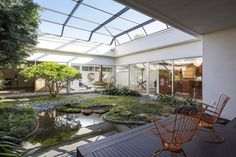 Taking cues from a traditional Japanese home, the residence arranges itself around a courtyard garden boasting mature plants and a koi pond. Japanese Style House, Japanese Interior Design, Indoor Pond, Indoor Courtyard, Indoor Trees, Indoor Garden, Rustic Sunroom, Koi Pond Design, Modern Home Offices