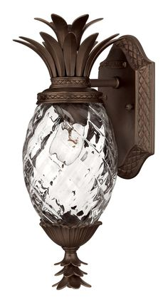 Features: -Pineapple-shaped lantern. -Clear optic glass shade. -Copper Bronze finish. Product Type: -Wall lantern. Finish: -Copper bronze. Fixture Material: -Metal. Shade Material: -Glass. Bul