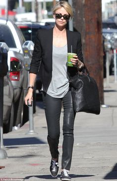 The fruits of her labour: Charlize Theron showcased her slender legs in leather trousers on Tuesday