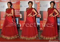 Bollywood and South Indian actress Tamanna in beautiful red,maroon and pink combination half saree. Designed by Tarun Tahiliani at SIIMA 2014. She looked gorgeous in half saree. Embroidered mirrors all over lehenga and gold border, pink and red georgette dupatta. Paired with designer cap sleeves saree blouse for back.