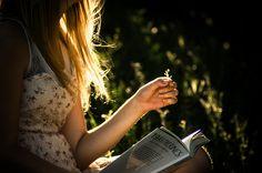 Menina com livro num jardim