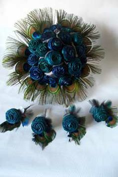 Two toned aqua and blue flax flowers with a collar of peacock feathers and matching button holes.