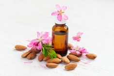 Almond oil in a small bottle, almond flowers and nuts