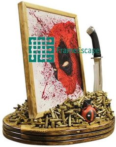 This Deadpool piece features a custom acrylic painting of the Merc with a Mouth, a shiny new knife, a custom painted hand grenade, and over 800 bullet casings (.556, .45, and 30-30 calibers).  The painting is mounted within an aspen frame, and it is all mounted onto a thick aspen base.  Available at www.FrameEscape.com