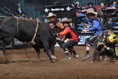 Silvano Alves rides Tribal Tuffs for 84.5. Shorty Gorham, Frank Newsom, and Jesse Byrne save him during the first round of the Oklahoma City Built Ford Tough series, PBR, Dickies, photo by Andy Watson with Bullstockmedia.com