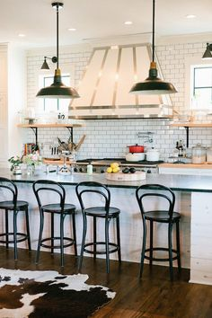 Amazing kitchen features a black vintage barn pendants illuminating an super long kitchen island topped with black countertop lined with black bentwood counter stools.