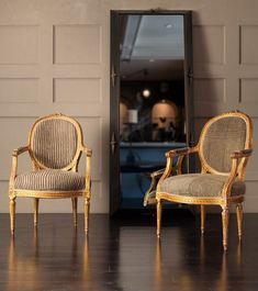 Pair of Louis XVI Carved and Gilded Chairs with Antique African Upholstery. France, 18th Century. Gilded wood. Shown with Compass Dressing Mirror by Blackman Cruz represented artist Lika Moore.