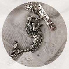 Necklace Silver Mermaid,charms 24 inch chain NEW necklace With silver Mermaid and charms,one says Faith,with pearl. Length is 24 inches. New mermaid is 3 inches Jewelry Necklaces