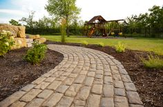 Cobblestone walkway with country-like landscape. All plants and landscaping done by McKay Nursery.
