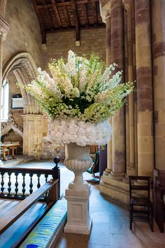 Tall white delphinium with a collar of hydrangea displayed in a stone urn