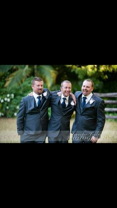 Groomsmen attire, charcoal suits with vest, navy ties and handkerchiefs with pale pink handmade fabric flowers with twig