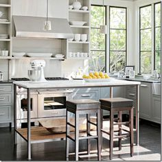 contemporary white and gray kitchen. planked backsplash, steel windows, open shelving, and industrial/rustic island