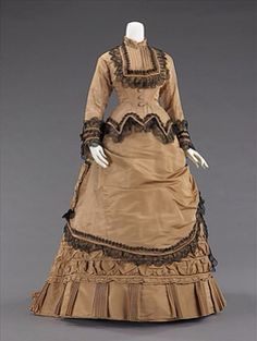 Early 1870s bustle dress, American, silk. Dress worn for promenading and visiting. Skirt decoration in this period was often achieved by using two separate skirts, with an overskirt being the main source of decoration and the puffing for the bustle. The dense textiles preferred were covered in trimming, beadwork, puffs and bows to visually elevate them further. (Metmuseum.org)