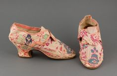 Pair of lady's buckle shoes, 1760-1769. Cream silk brocade woven with a floral design in red and blue, Louis heels, round toes.