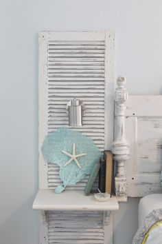 Beachy nightstands, custom made shutter nightstands. Paired with reclaimed door headboard, using parts and pieces from old tables, and beds. Nautical sconce mounted to shutter. Large, aqua painted sea fan, paired with starfish. Theraggedwren.blogspot.com