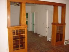 Arts and Crafts Bookshelf Room Divider. Honey colored oak arts and crafts style bookshelves and columns dividing the front living room from the dining room in a modest house. The craftsmanship that has endured for decades is amazing.