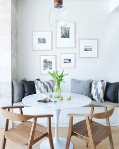 """Pro tip: mix and match bench seating with dining chairs. Though this table may look tiny, the clever pairing of wishbone chairs with a built-in bench (which doubles as storage) allows for more seating space than meets the eye. """"A round table controls traffic in a small space,"""" explains designer Jamie Deck, director of Shift Interiors. Up to four people can cozy up on the bench, and by adding a few more chairs along the curve of the table, you've got room for all your favourite dinner-party…"""